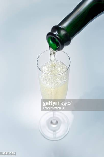 Pouring glass of sparkling wine, close-up