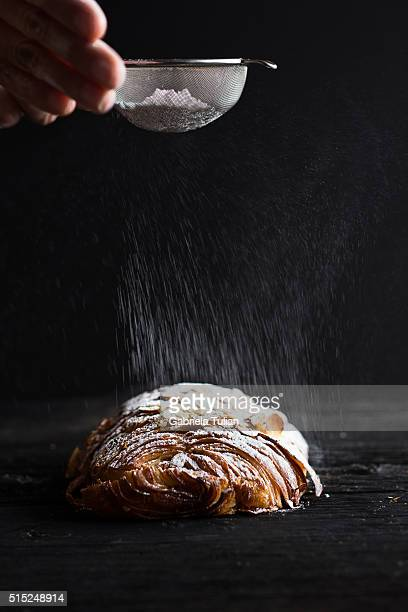 Pouring icing sugar on chocolate croissant