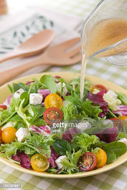 Pouring Italian Dressing on Salad
