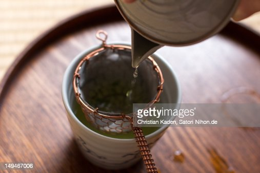 Pouring Japanese tea into small white cup : Stock Photo