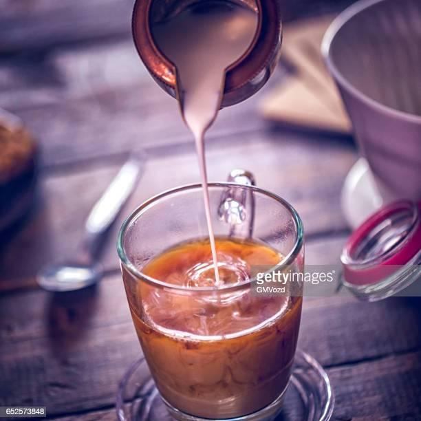 Gieten van melk in het kopje koffie