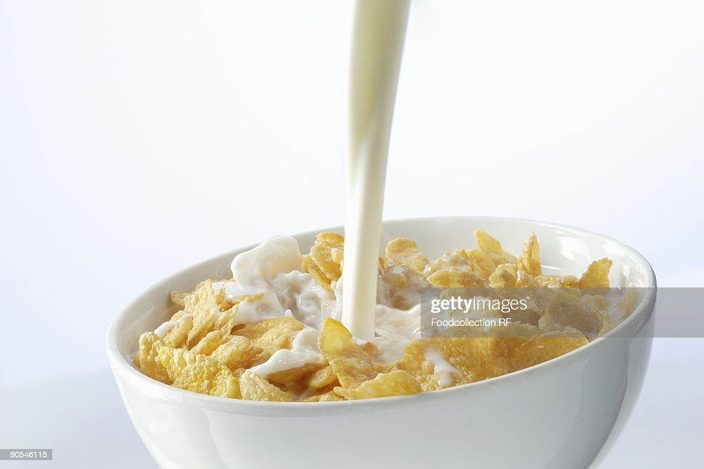 Pouring milk over cornflakes, close up