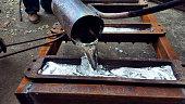 Workers pour molten aluminum into ingots