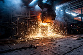 Pouring of liquid metal in open-hearth furnace. Production process in the steel mill. Working open hearth furnace.