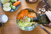 Pouring olive oil from bottle onto cabbage and carrot salad. Selective focus