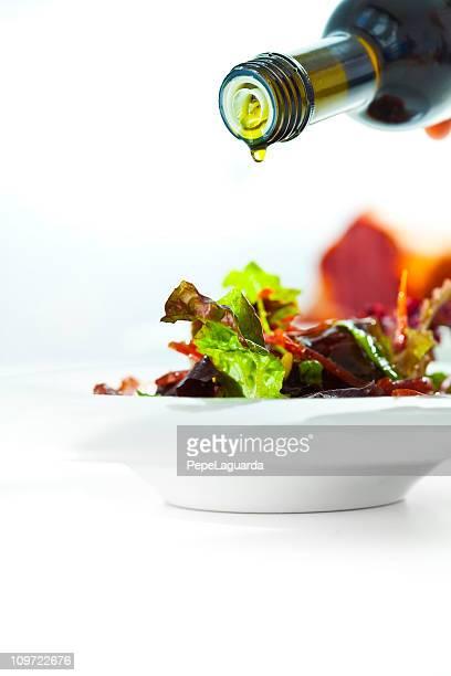 オリーブオイルを注ぐ新鮮なサラダ