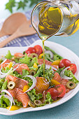 Pouring Olive Oil onto Marinated Salmon Salad