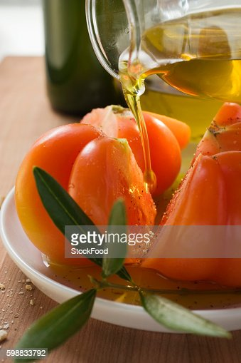 Pouring olive oil over tomatoes