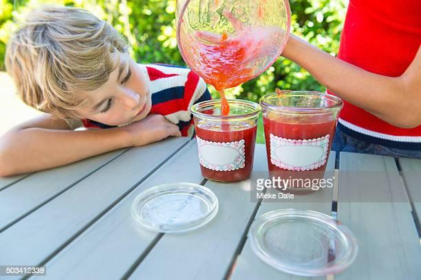 Pouring plum jam into jars