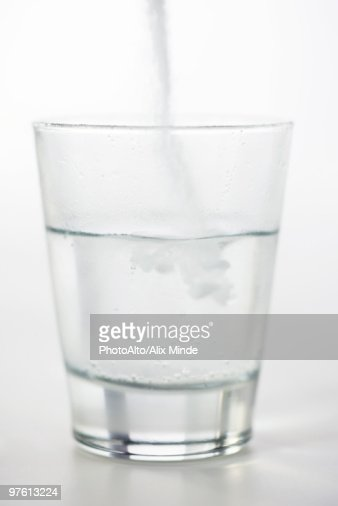 Pouring powdered medicine into glass of water