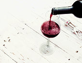 Pouring red  wine from bottle in wine glass on vintage white wooden table  with copyspace.