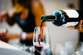 Man pouring red wine to wine glass.
