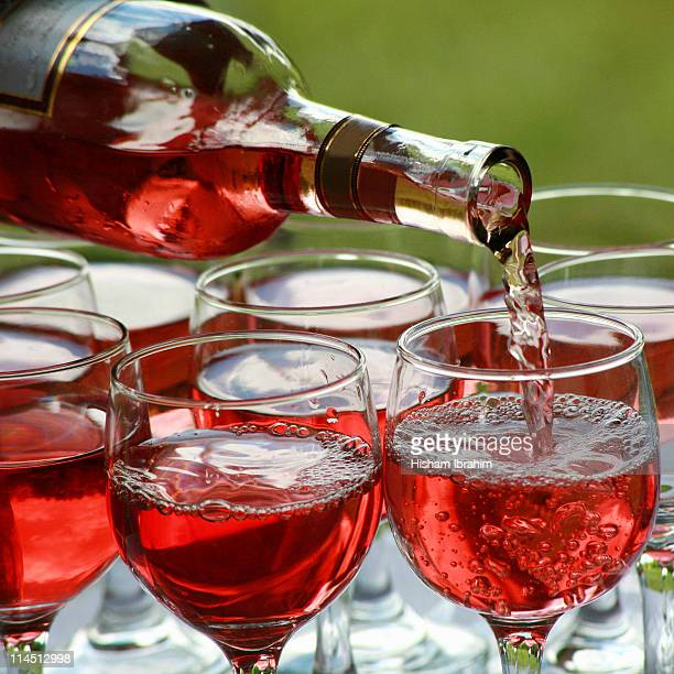 Pouring Rose Wine Bottle into Glasses