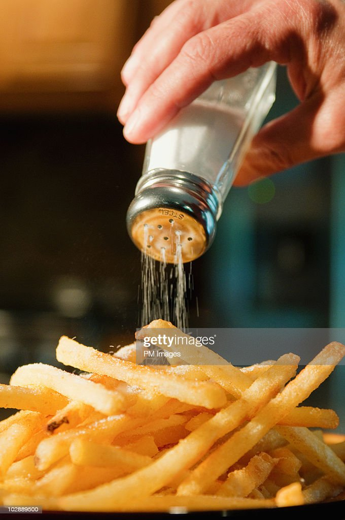 Pouring salt on french fries : Stock Photo