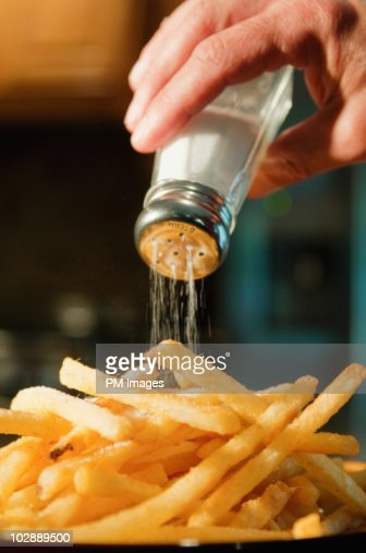 Pouring salt on french fries