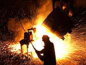 A worker pours steel at a foundry.