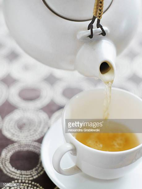 Pouring Tea from White Teapot