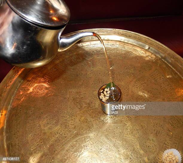 Pouring the tea with fresh mint and pine nuts