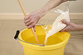 Pouring wallpaper paste in to a bucket of water and stirring with a stick
