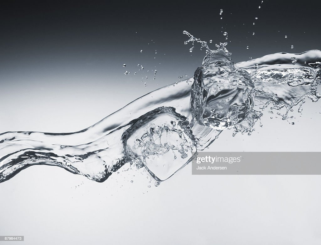Pouring water and ice cubes : Stock Photo