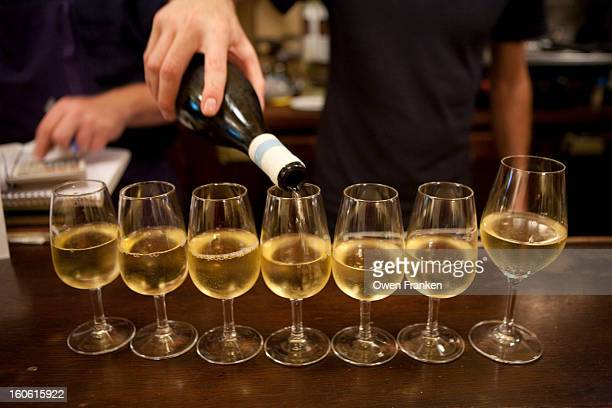 Pouring white wine at a bar