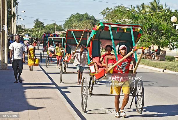 Pousse-pousse rickshaw pullers and passengers; Toliara, Madagascar