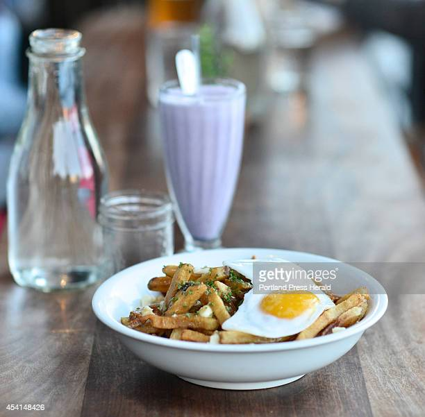 Poutine with duck egg duck gravy and cheese curds at Duck Fat on Monday July 18 2014