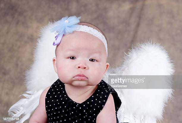 Pouting baby girl with white feather wings.