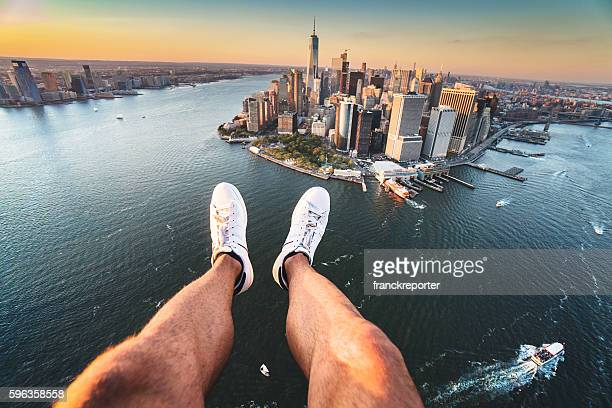 Pov of human leg with Manhattan skyline from helicopter
