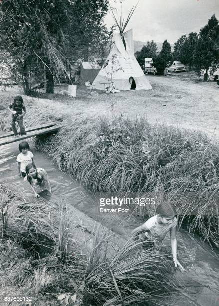Pow Wow Lures Indians from several States These Indian children kept cool Saturday afternoon in an irrigation ditch on the Foothills Recreation...