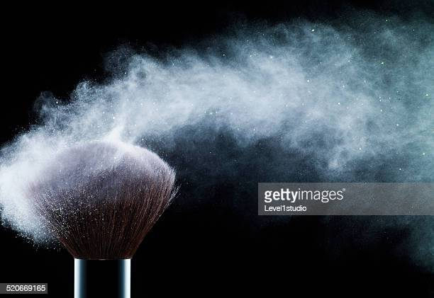 Powder blowing from cosmetic brushes