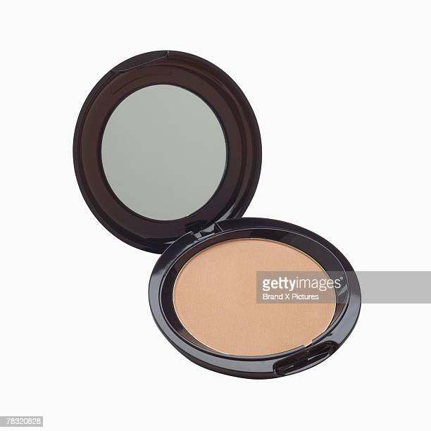 Powder compact and mirror