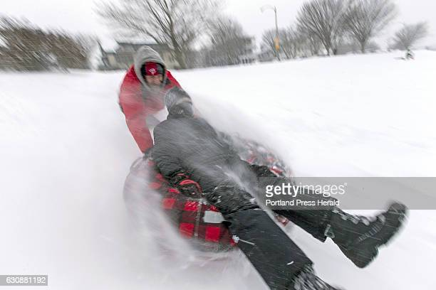 Powdery snow flows around Emerson Dolan as stepfather John Hart gives him a push down the sledding hill on the Eastern Prom