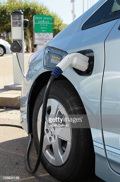 A power cable from a vehicle charging station is seen plugged into the side of a Toyota Prius plugin hybrid August 25 2010 in San Francisco...