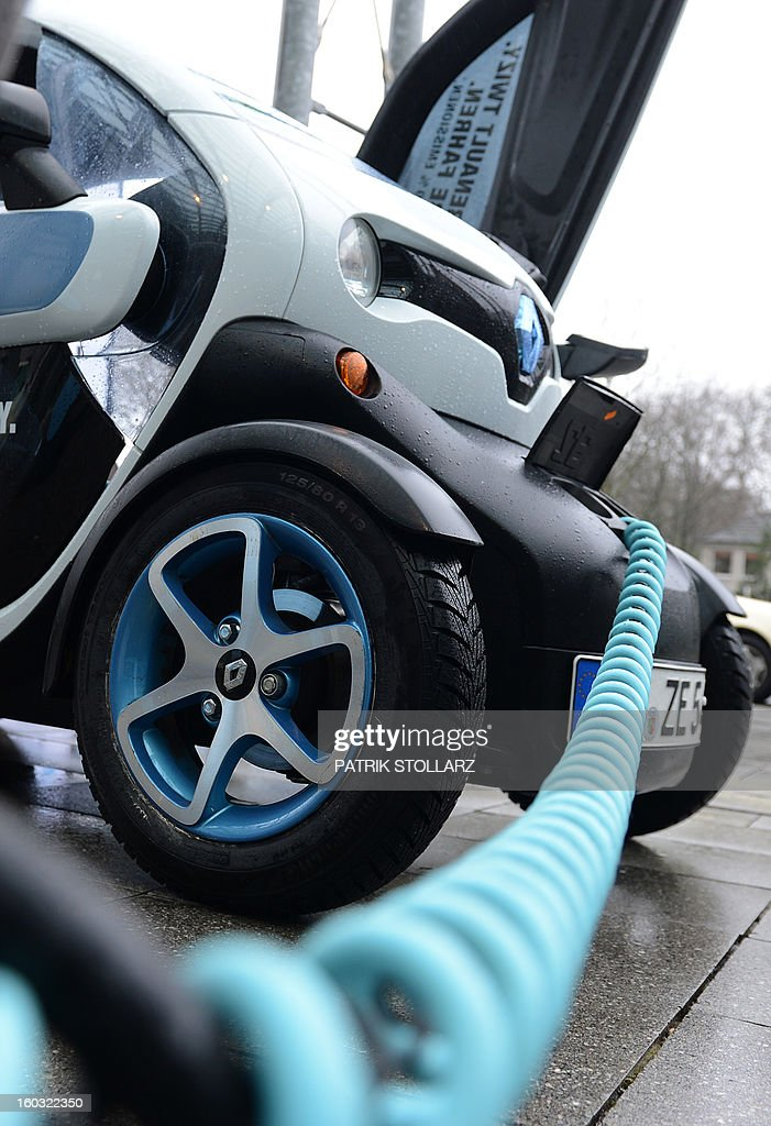 A power cable stucks in a Renault Twizy for charging at a power plug during the CAR-Symposium in Bochum, western Germany, on January 29, 2013. Automotive distributers and major car companies discuss about the future of the automotive industries.