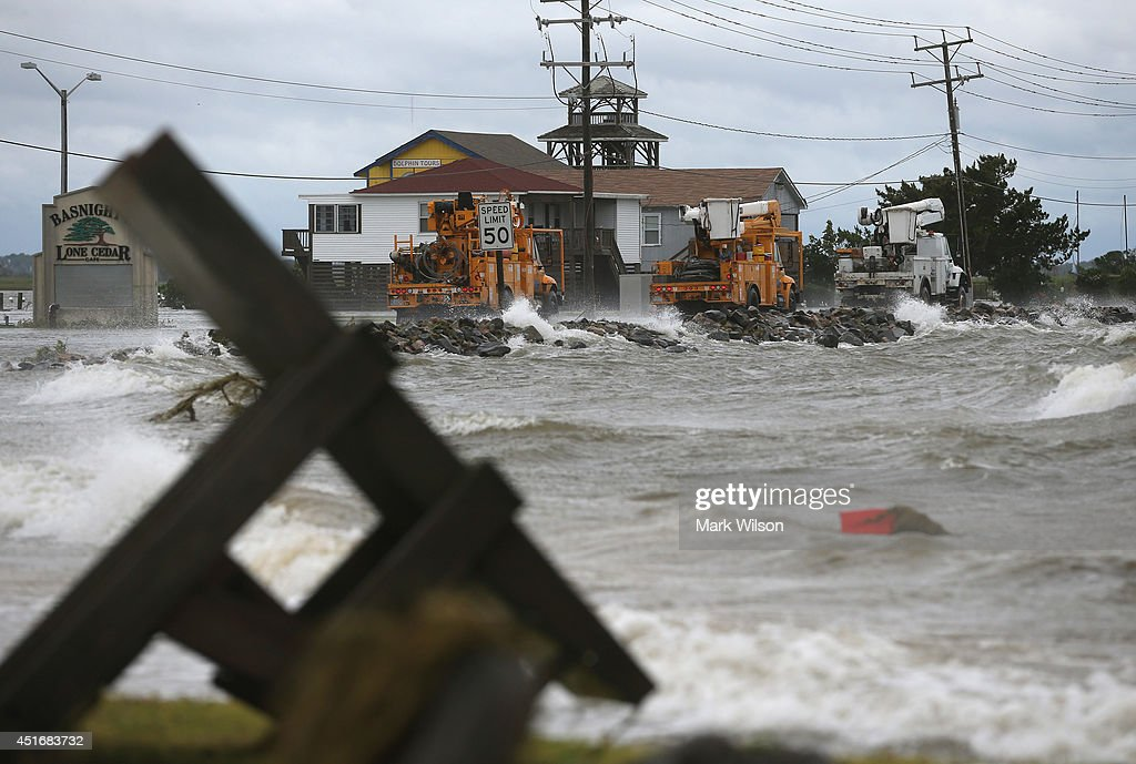Power company trucks travel along Highway 64 after flooding caused by Hurricane Arthur July 4, 2014 in Nags Head, North Carolina. Hurricane Arthur hit North Carolina's outer banks overnight causing wide spead power outages, flooding and damage.