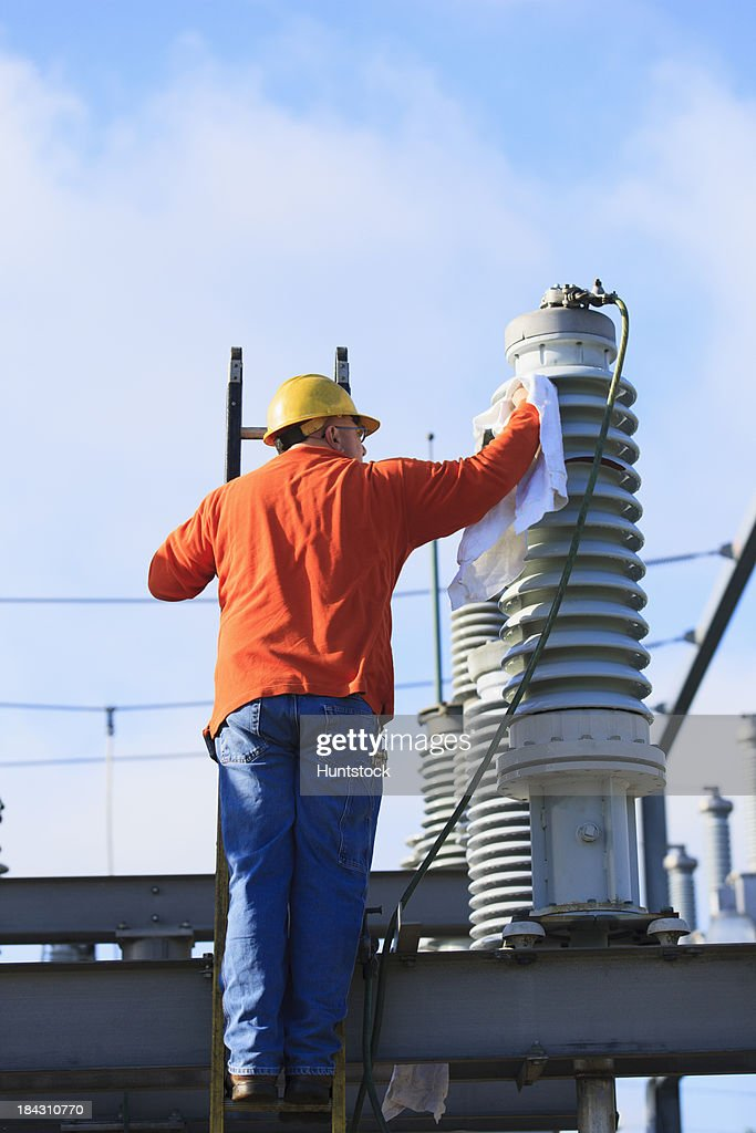 Power engineer cleaning a fluid filled high voltage insulator