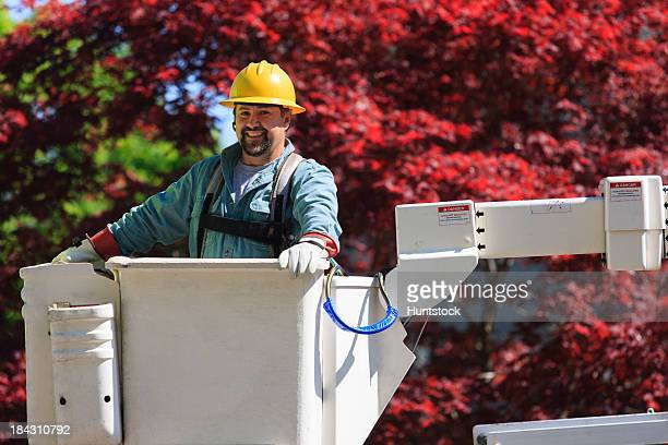 Power engineer in lift bucket wearing a safety harness and insulated gloves