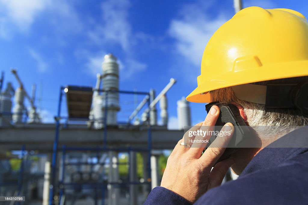 Power engineer talking on a mobile phone at high voltage distribution station