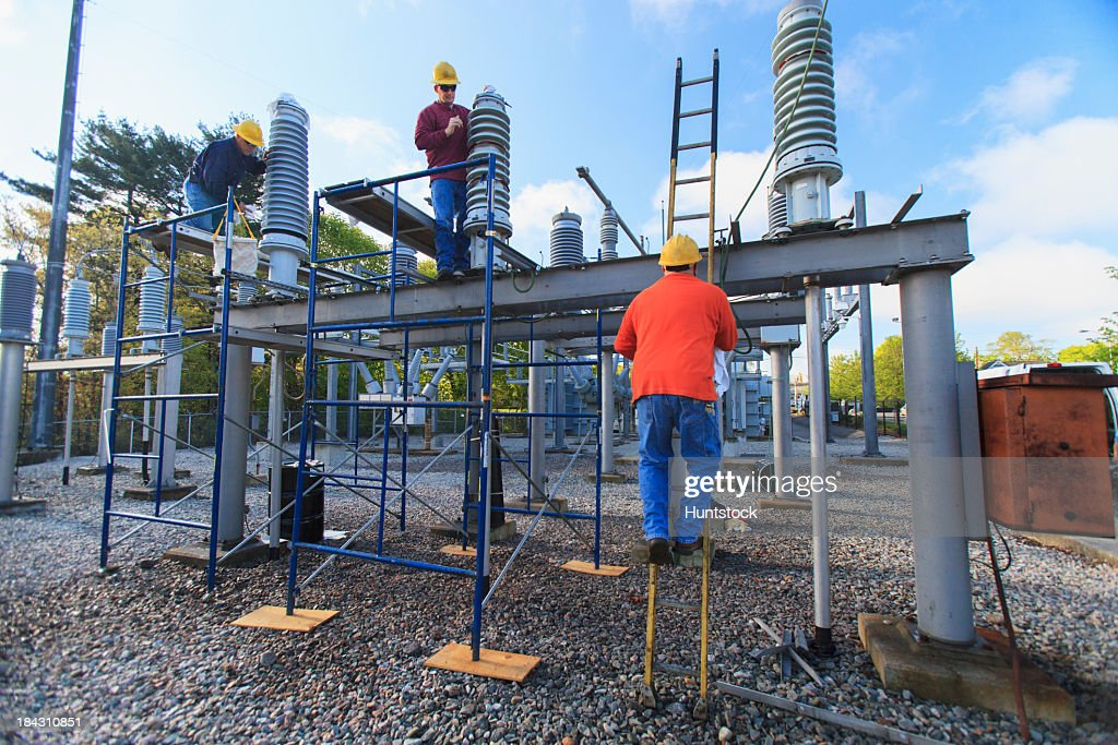 Power engineers working on high voltage power distribution station
