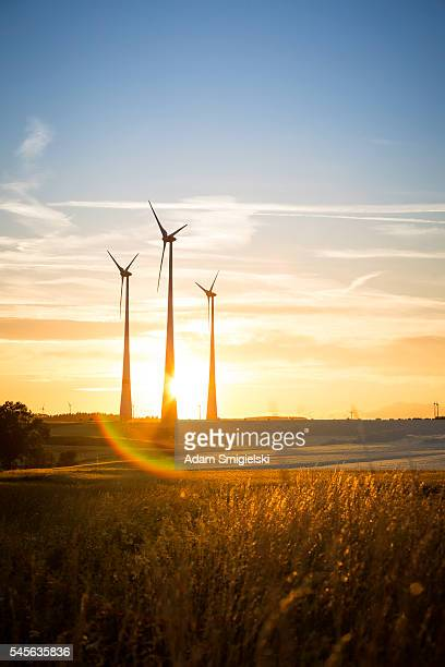 power generating wind turbines in the countryside in the evening
