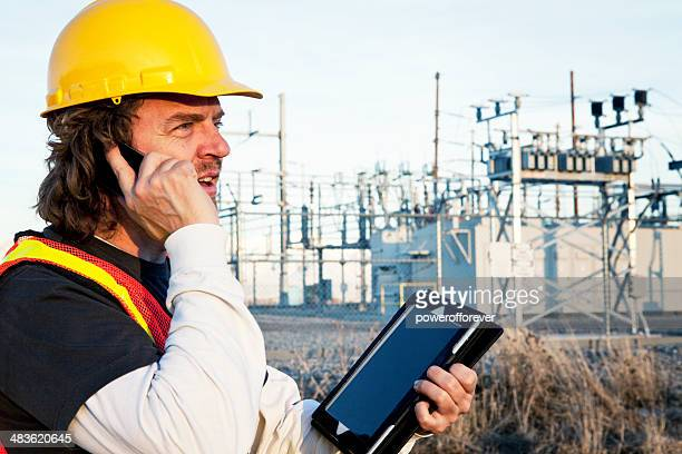 Power Line Technician Using Phone and Tablet