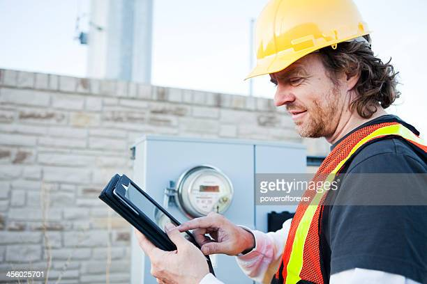 Power Line Technician Using Tablet Computer