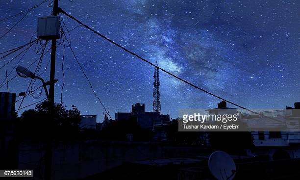 Power Lines And Buildings Against Star Field At Night