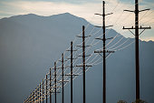 Power lines in rows across the landscape, against a mountain and sunset sky.
