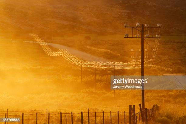 Power lines on road in grassy remote landscape