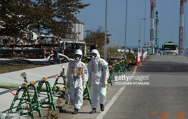 Power plant workers walk along a road at the Fukushima Daiichi nuclear power plant in Okuma Fukushima prefecture on October 9 2015 Tokyo Electric...
