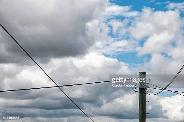 Power pole against cloudy sky.