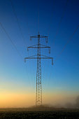 power poles with fog at sunset