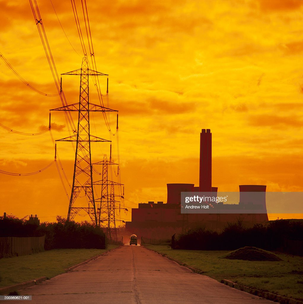 Power Station and electricty pylons beside dirt track, silhouette : Stock Photo